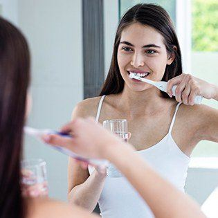 woman using electric toothbrush