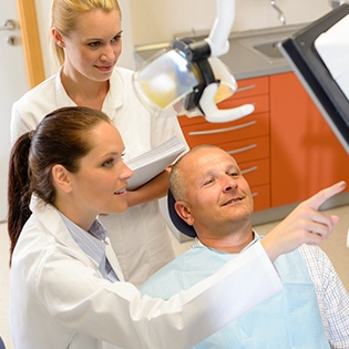 A male patient looking at a screen that is being discussed by his dentist