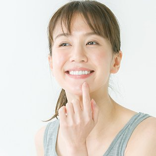 A smiling woman pointing to her mouth