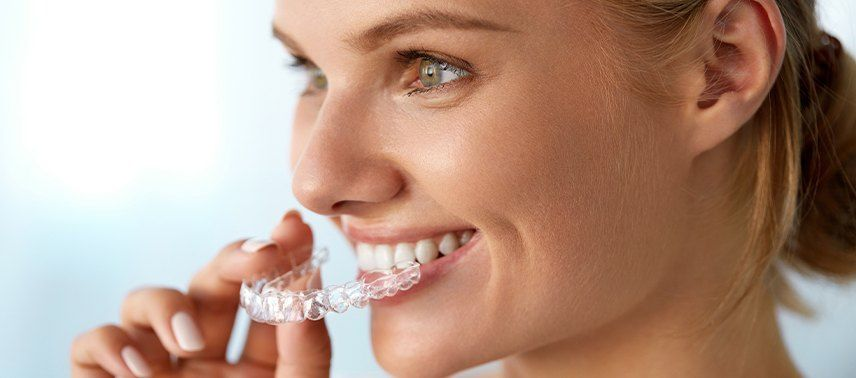 woman putting in invisalign clear tray