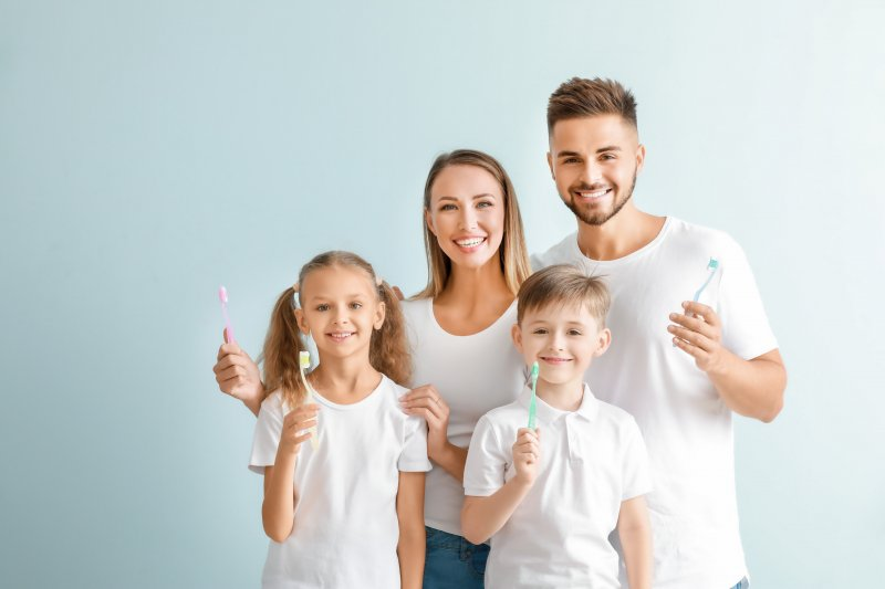 a husband and wife with their two children all holding toothbrushes