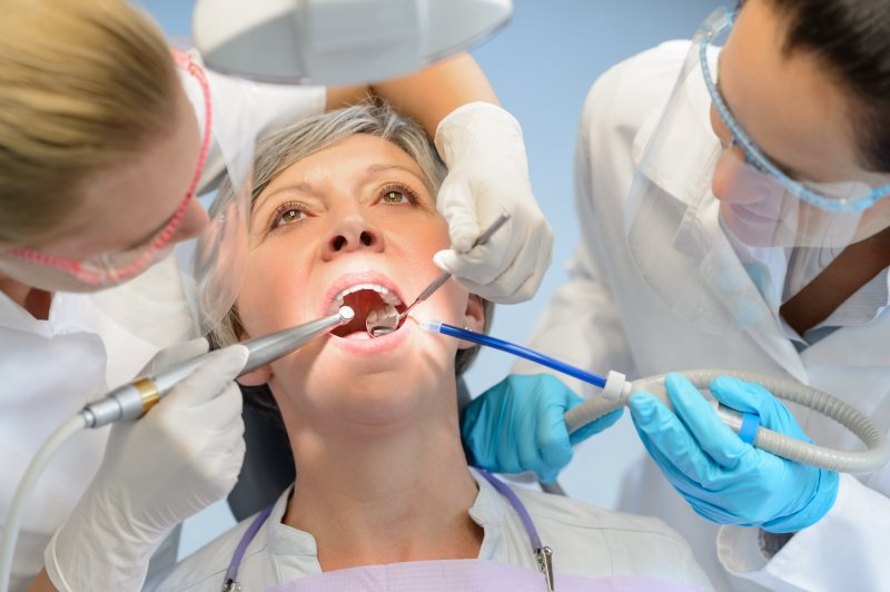 a dentist and dental hygienist performing dental work on an elderly patient