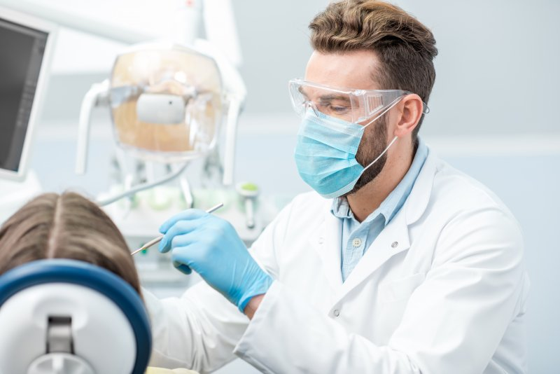 a dentist wearing personal protective equipment while providing treatment to a patient