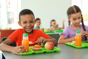 Two children eating school lunches in bright cafeteria