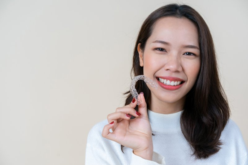 a young woman wearing a white sweater and holding an Invisalign aligner in her hand