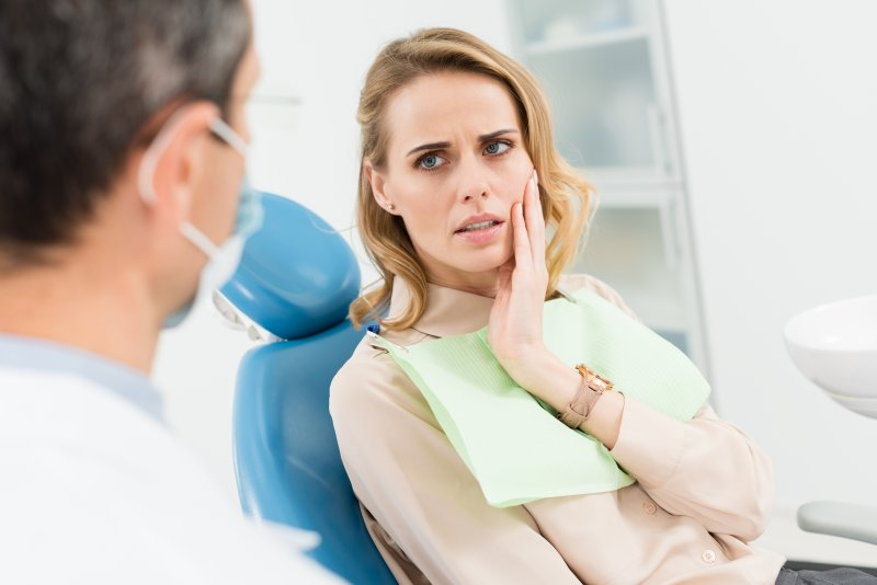 a young woman holding her cheek and listening to her dentist discuss treatment options for a loose tooth