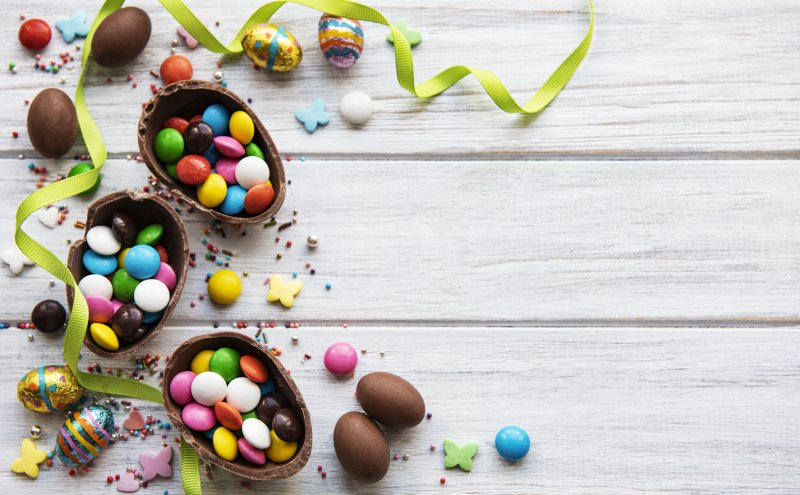 three chocolate eggs that contain jelly beans and chocolate candies for Easter