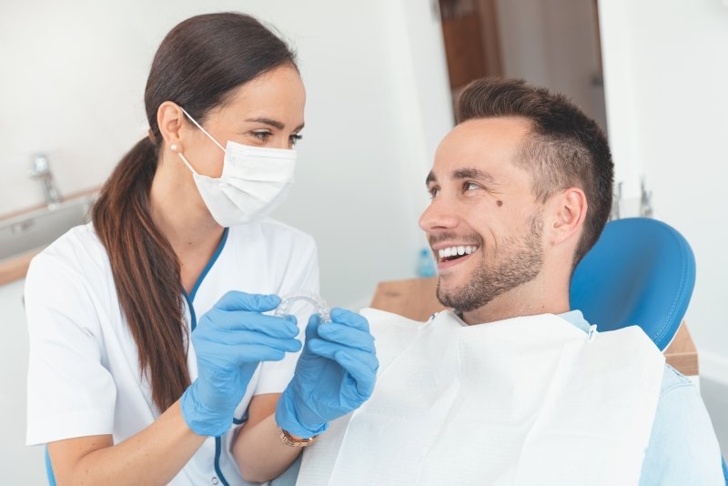 Dentist and patient smiling while discussing Invisalign